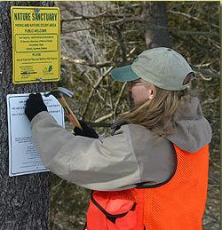 woman posting conservation sign on tree